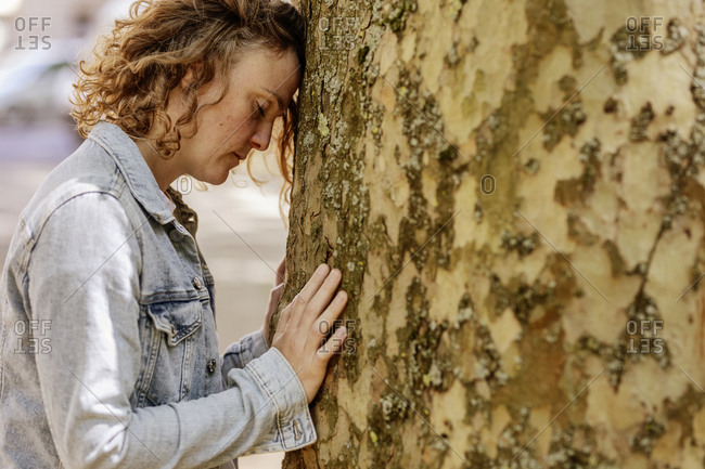 Sad mid adult woman with eyes closed leaning on tree trunk in park