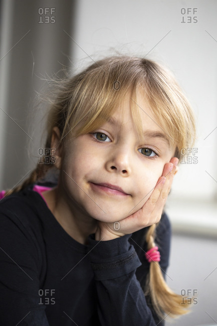 Close-up of cute girl with hand on chin sitting at home