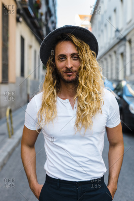 Stylish mid adult man with long hair wearing hat while standing on street in city