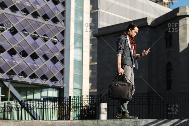 Trendy man with handbag using smart phone while walking in city