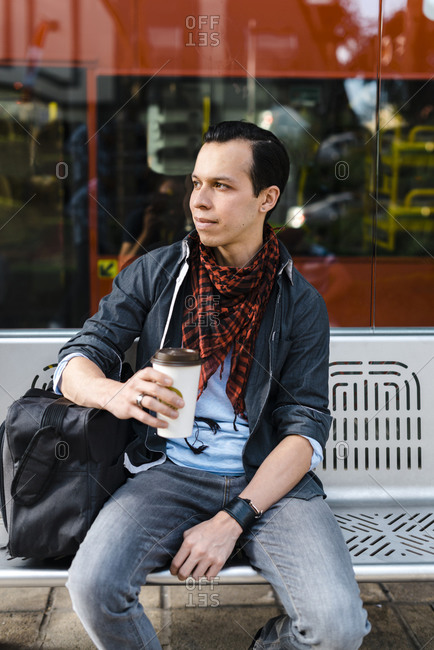 Man in casuals having coffee while waiting for bus at station