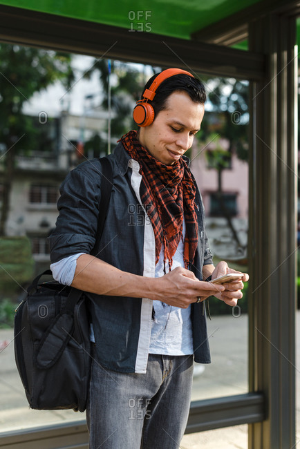 Trendy man using smart phone while listening music through headphones at bus stop