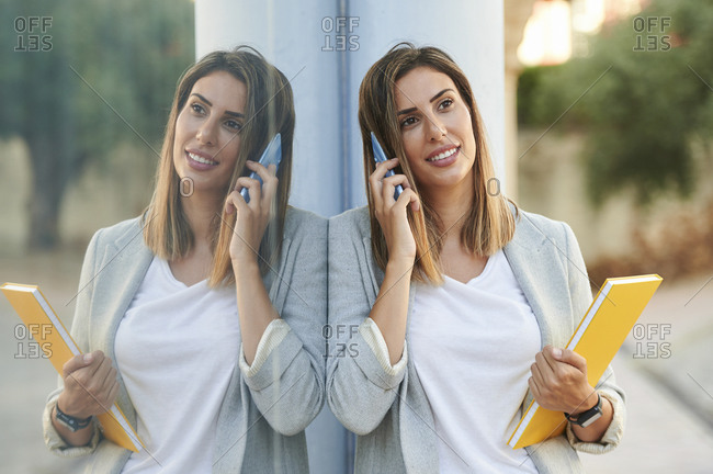Reflection of businesswoman on window glass while talking on mobile phone