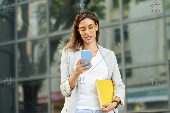 Businesswoman text messaging through smart phone outside office building