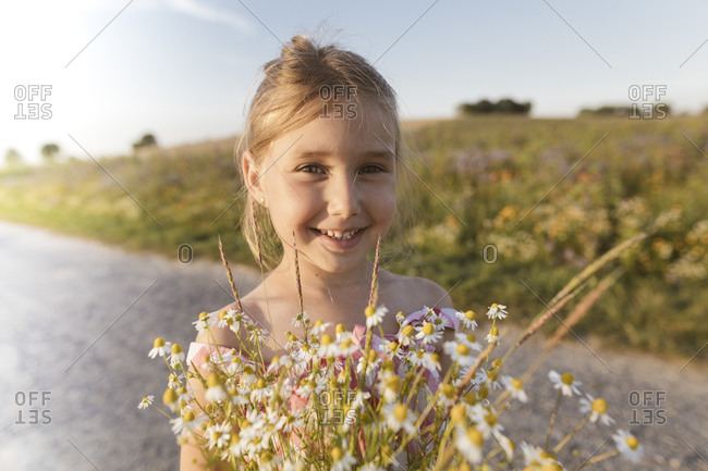 Close-up of smiling girl holding flowers on road against sky at sunset