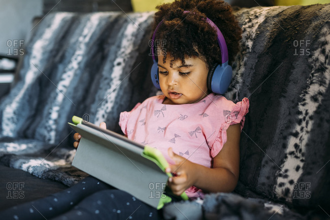 Baby girl with curly hair using digital tablet while sitting on sofa at home