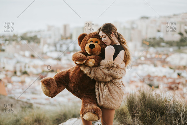 Woman with eyes closed hugging teddy bear while standing against city