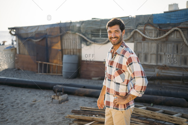 Smiling handsome man standing against built structure at beach