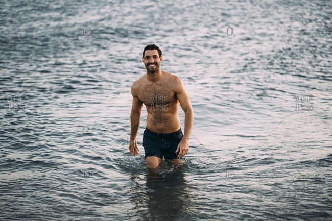 Shirtless smiling mid adult man wading in sea during sunset