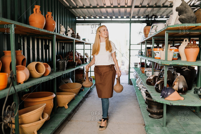 Smiling female owner holding potteries while standing amidst shelves in workshop