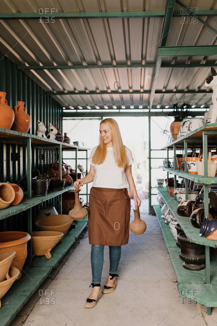 Smiling female owner holding potteries while walking amidst shelves in workshop