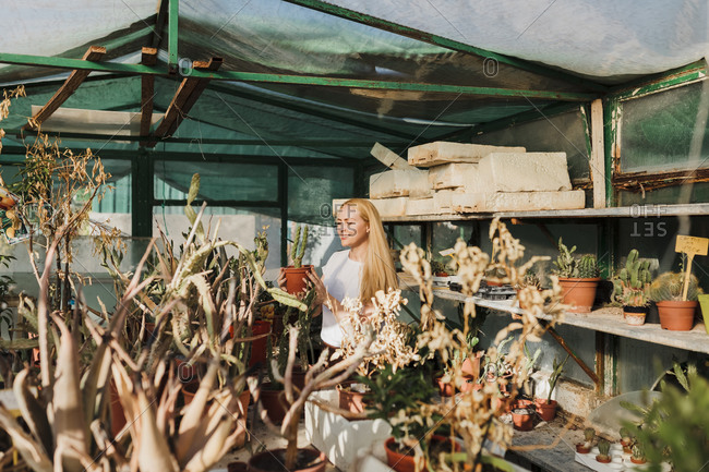 Smiling mid adult woman with blond hair holding cactus while standing in plant nursery