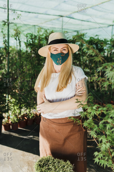 Female owner wearing mask and hat with arms crossed standing by plants at greenhouse