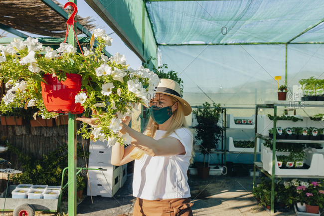 Female owner wearing mask and hat taking care of flowers in plant nursery