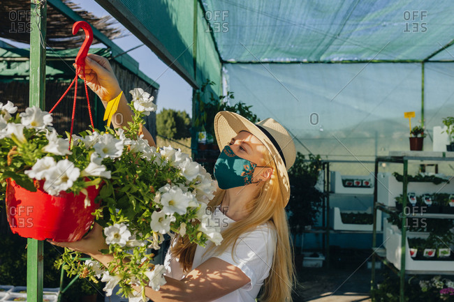 Mid adult woman wearing mask and hat hanging flowers in plant nursery