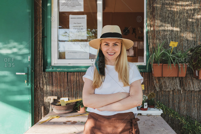Smiling female owner wearing hat with arms crossed standing by table outside plant nursery