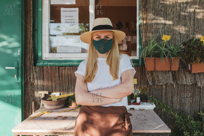 Female owner wearing hat and mask with arms crossed standing by table outside plant nursery