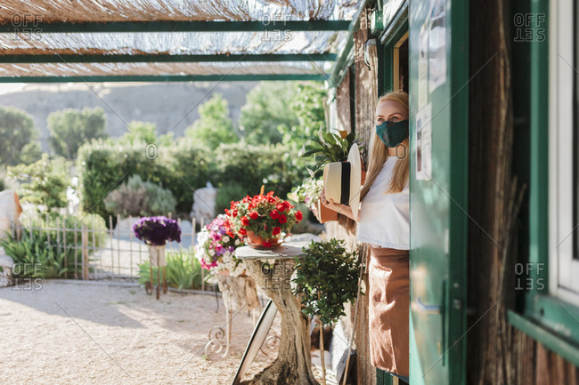 Female owner wearing mask looking away while standing at entrance of plant nursery