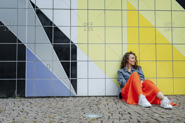 Young woman sitting on the ground in city- leaning on tiled wall