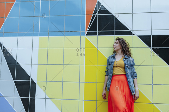 Young woman leaning on colorful tiled wall looking sideways