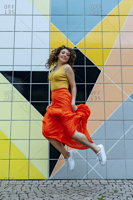 Young woman jumping in front of colorful tiled wall