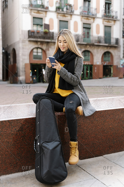Young woman with violin case using smartphone in city