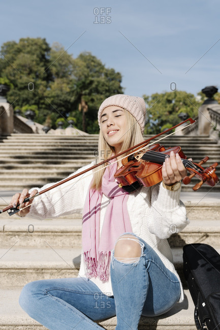 Blond young woman playing violin sitting on stairs