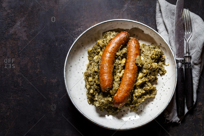 Plate of smoked sausages with kale