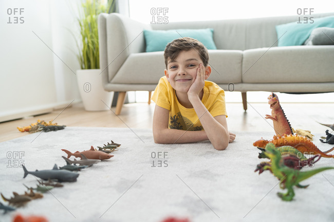 Smiling boy with hand on chin lying by toy animals on carpet in living room