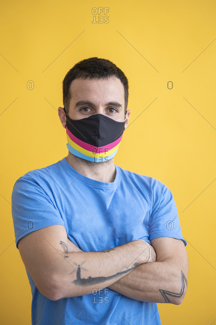 Close-up of man wearing multi colored mask with arms crossed standing against yellow background
