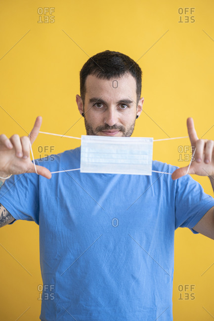 Close-up of mid adult man holding mask while standing against yellow background