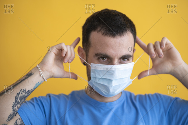 Close-up of man wearing mask looking away against yellow background