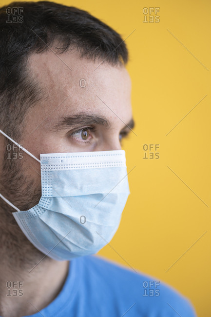 Close-up of thoughtful mid adult man wearing mask against yellow background