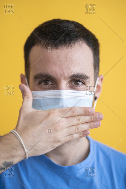 Close-up of mid adult man wearing mask covering mouth with hand against yellow background