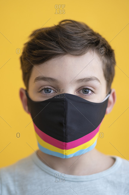 Close-up of boy wearing multi colored mask against yellow background