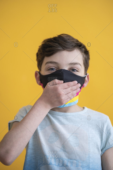 Close-up of boy wearing mask covering mouth with hand against yellow background