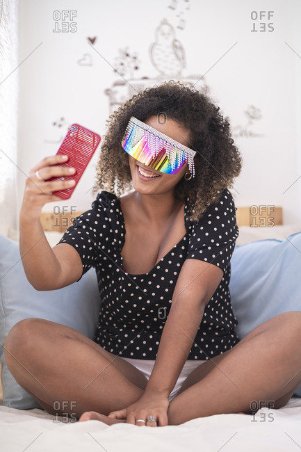 Woman wearing multi colored sunglasses taking selfie with smart phone on bed at home