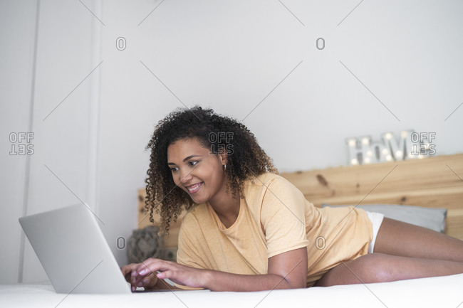 Smiling young woman with curly hair using laptop while lying on bed at home