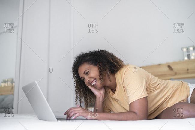 Cheerful woman with curly hair using laptop while lying on bed at home