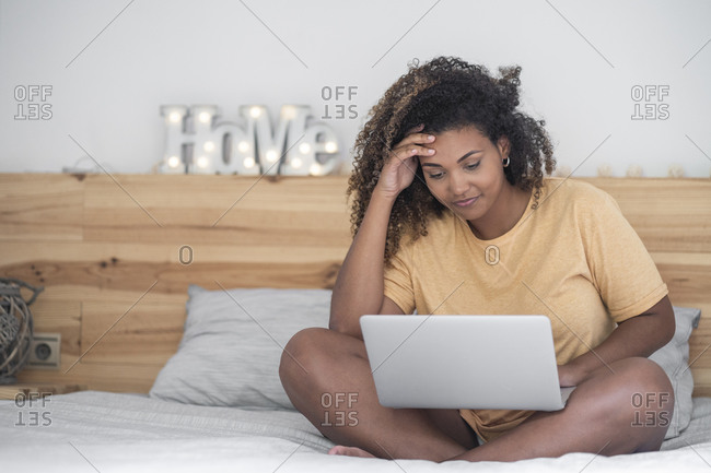 Young woman with curly hair using laptop while sitting on bed