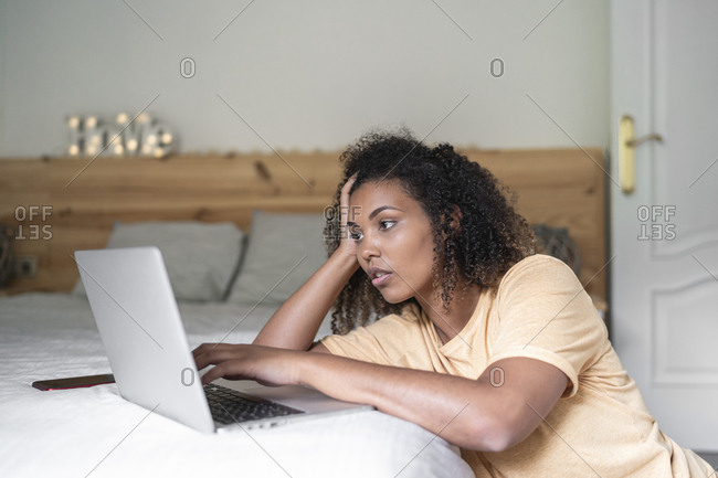 Stressed young woman with head in hand using laptop on bed at home