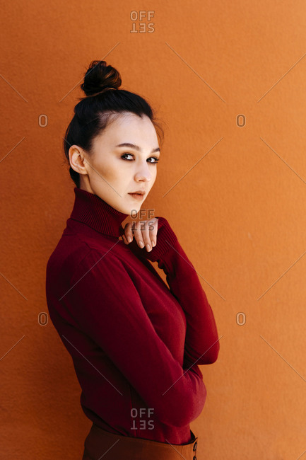 Young woman wearing turtleneck long-sleeved top against orange wall