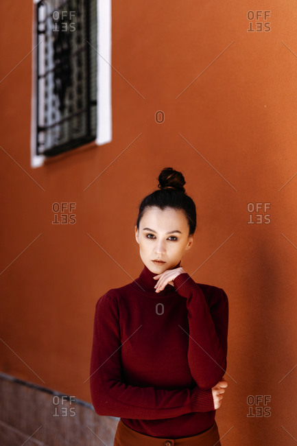 Beautiful woman with hand on chin standing by wall