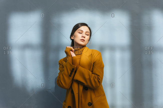 Beautiful woman with eyes closed in wearing yellow winter coat against gray wall