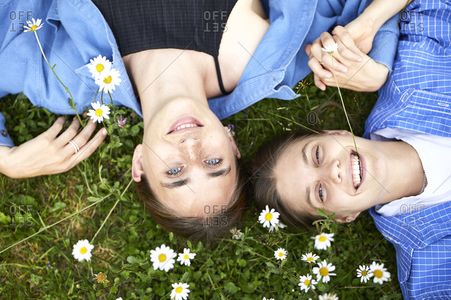 Close-up of smiling young friends lying on grassy land in garden