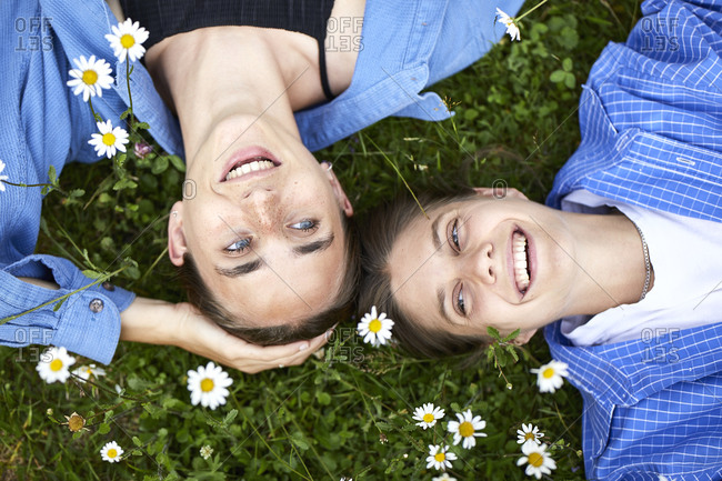 Close-up of cheerful young friends relaxing on grassy land in garden