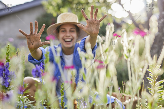 Cheerful woman wearing hat showing dirty hands while sitting amidst plants in garden