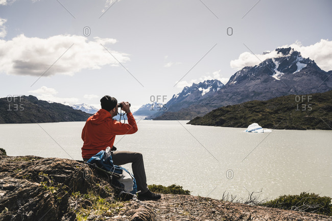 Man looking at Grey Glacier with binocular at Torres Del Paine National Park- Patagonia- Chile- South America
