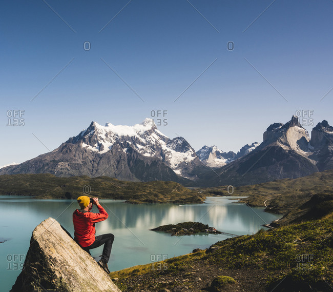 Man looking through binocular at Lake Pehoe in Torres Del Paine National Park- Chile Patagonia- South America