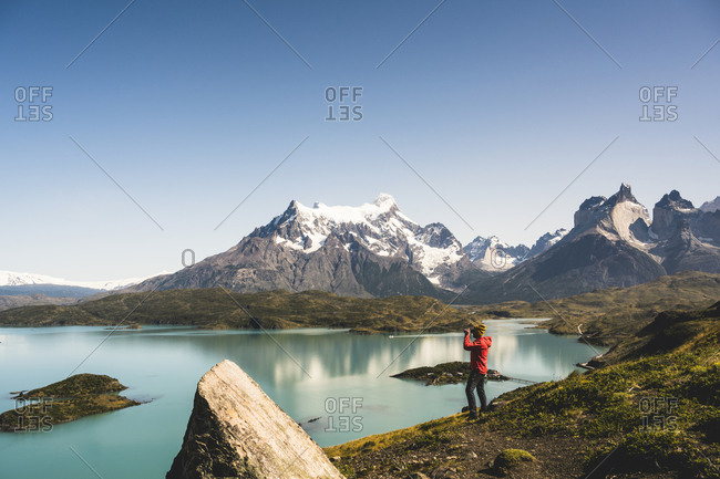 Man looking at Lake Pehoe through binocular in Torres Del Paine National Park- Chile Patagonia- South America